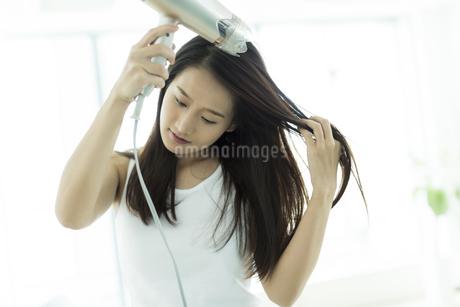 ドライヤーで髪を乾かす若い女性の写真素材 [FYI00497343]