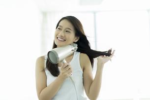 ドライヤーで髪を乾かす若い女性の写真素材 [FYI00497346]