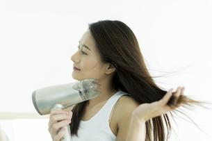 ドライヤーで髪を乾かす若い女性の写真素材 [FYI00497347]