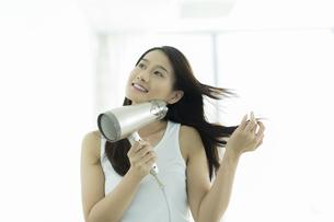 ドライヤーで髪を乾かす若い女性の写真素材 [FYI00497348]