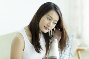 ドライヤーで髪を乾かす若い女性の写真素材 [FYI00497350]