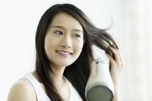 ドライヤーで髪を乾かす若い女性の写真素材 [FYI00497351]