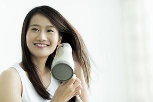 ドライヤーで髪を乾かす若い女性の写真素材 [FYI00497352]