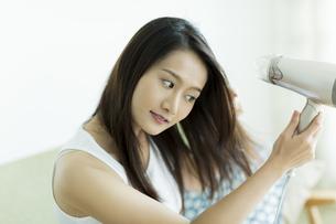ドライヤーで髪を乾かす若い女性の写真素材 [FYI00497353]