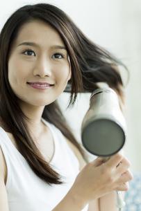 ドライヤーで髪を乾かす若い女性の写真素材 [FYI00497354]
