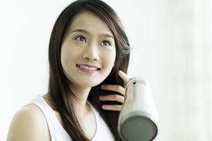 ドライヤーで髪を乾かす若い女性の写真素材 [FYI00497355]