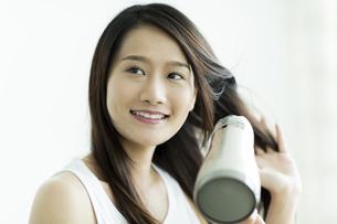 ドライヤーで髪を乾かす若い女性の写真素材 [FYI00497356]