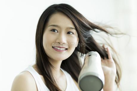 ドライヤーで髪を乾かす若い女性の写真素材 [FYI00497357]