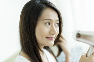 ドライヤーで髪を乾かす若い女性の写真素材 [FYI00497358]