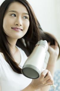 ドライヤーで髪を乾かす若い女性の写真素材 [FYI00497359]