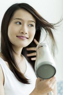 ドライヤーで髪を乾かす若い女性の写真素材 [FYI00497360]
