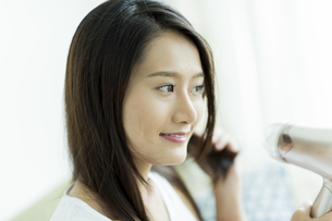 ドライヤーで髪を乾かす若い女性の写真素材 [FYI00497361]