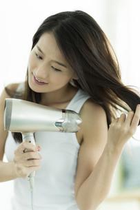 ドライヤーで髪を乾かす若い女性の写真素材 [FYI00497362]