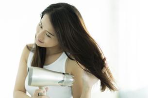 ドライヤーで髪を乾かす若い女性の写真素材 [FYI00497364]