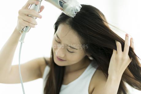 ドライヤーで髪を乾かす若い女性の写真素材 [FYI00497365]