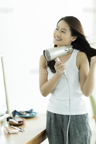 ドライヤーで髪を乾かす若い女性の写真素材 [FYI00497366]