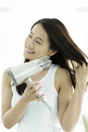 ドライヤーで髪を乾かす若い女性の写真素材 [FYI00497367]