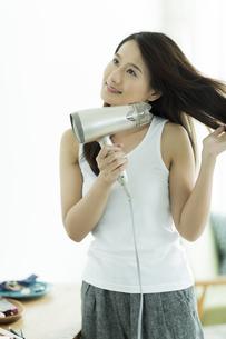 ドライヤーで髪を乾かす若い女性の写真素材 [FYI00497368]