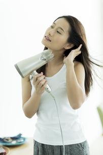 ドライヤーで髪を乾かす若い女性の写真素材 [FYI00497369]