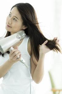 ドライヤーで髪を乾かす若い女性の写真素材 [FYI00497370]