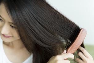 髪をとかす若い女性の写真素材 [FYI00497371]