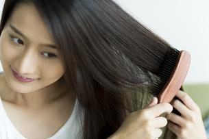 髪をとかす若い女性の写真素材 [FYI00497372]
