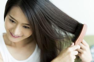 髪をとかす若い女性の写真素材 [FYI00497374]