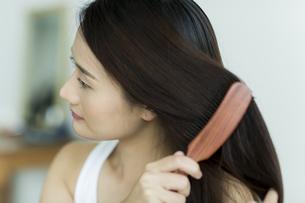 髪をとかす若い女性の写真素材 [FYI00497375]
