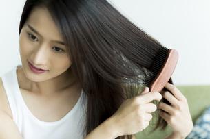 髪をとかす若い女性の写真素材 [FYI00497376]