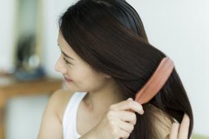 髪をとかす若い女性の写真素材 [FYI00497377]