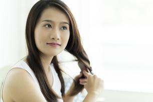 髪をとかす若い女性の写真素材 [FYI00497380]