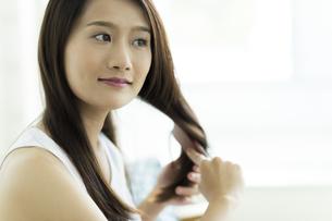 髪をとかす若い女性の写真素材 [FYI00497382]