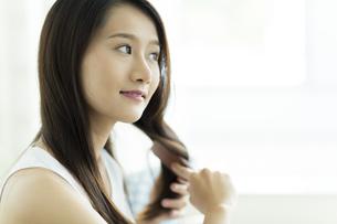 髪をとかす若い女性の写真素材 [FYI00497384]