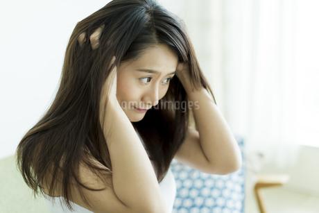 髪を触る若い女性の写真素材 [FYI00497386]