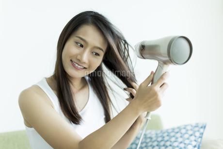 ドライヤーで髪を乾かす若い女性の写真素材 [FYI00497431]