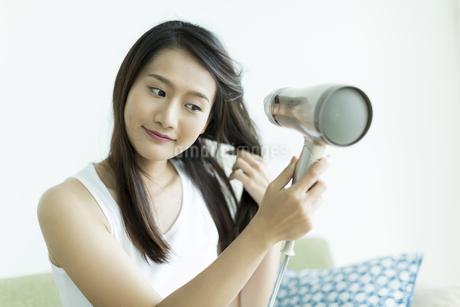 ドライヤーで髪を乾かす若い女性の素材 [FYI00497432]