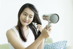 ドライヤーで髪を乾かす若い女性の写真素材 [FYI00497432]