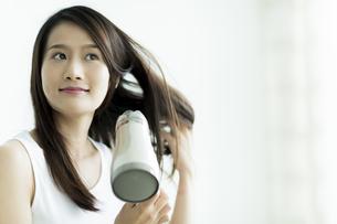 ドライヤーで髪を乾かす若い女性の写真素材 [FYI00497447]