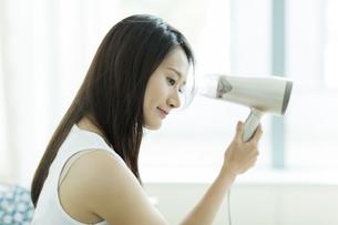 ドライヤーで髪を乾かす若い女性の写真素材 [FYI00497448]