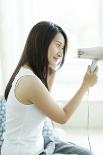 ドライヤーで髪を乾かす若い女性の写真素材 [FYI00497449]