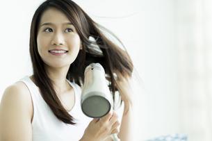 ドライヤーで髪を乾かす若い女性の写真素材 [FYI00497453]
