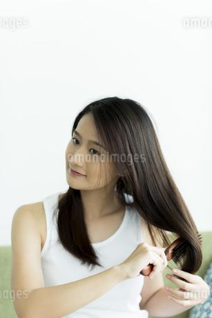 髪をとかす若い女性の写真素材 [FYI00497454]