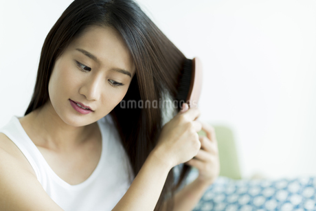 髪をとかす若い女性の写真素材 [FYI00497456]