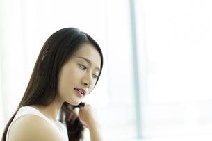 髪をとかす若い女性の写真素材 [FYI00497459]
