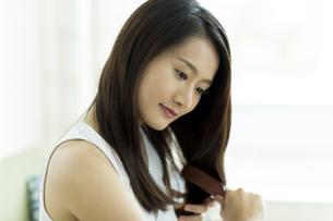 髪をとかす若い女性の写真素材 [FYI00497461]