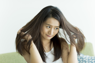 髪を触る若い女性の写真素材 [FYI00497467]