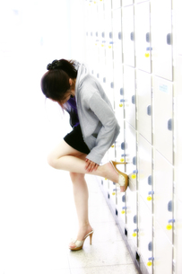 コインロッカーをバックに足を持ち上げる若い日本人女性の写真素材 [FYI00497601]