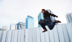 高層ビル群を背景に飛び上がる日本のサラリーマンの写真素材 [FYI00497772]