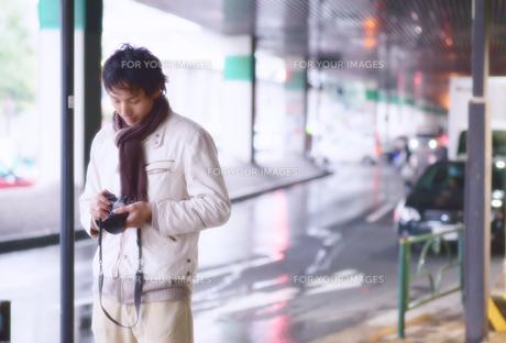 首にマフラーを巻きカメラを抱える男の写真素材 [FYI00497837]