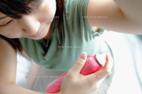 女性が脇に制汗スプレーを吹きかける様子の写真素材 [FYI00497918]